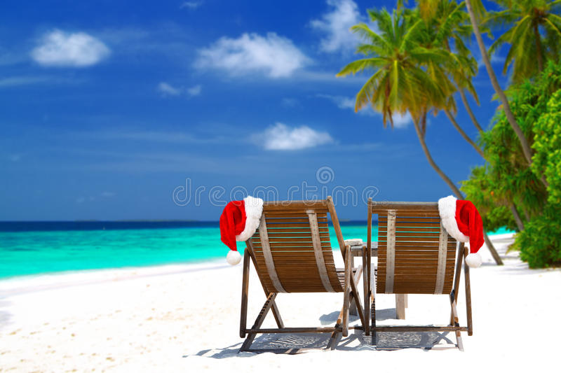 Christmas card. Or background - two sunloungers with Santa hats standing on beautiful tropical beach with palm trees, white sand and turquoise water on Maldives stock photos