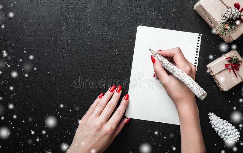Christmas card background - Woman hands with red nails writing letter with wooden pencil. royalty free stock photography