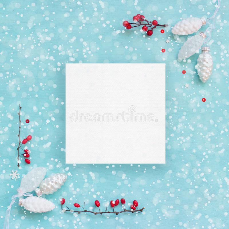 Christmas card or banner; White pine cones and red berries on blue background royalty free stock photo