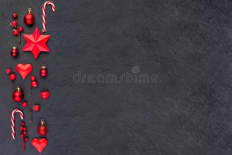 Christmas card on black. Red Christmas decor stars, candy and holly berries flat lay top view on dark background with copy space stock image