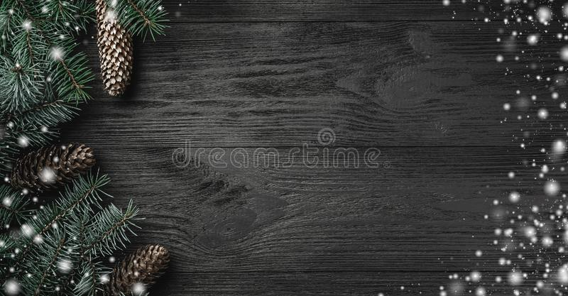 Christmas card. Black wood background with branches and fir cones in the side, top view. Xmas greeting card with snow effect stock photos