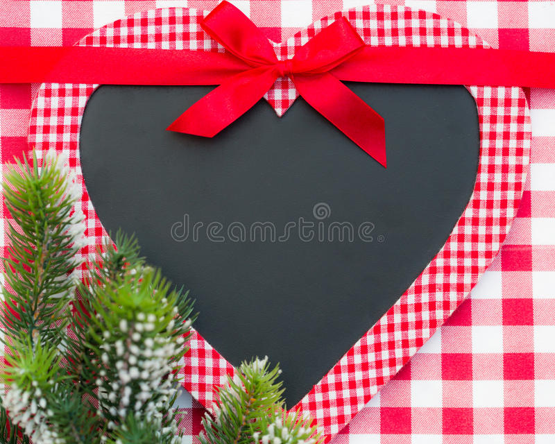 Christmas card blank in heart shape. With bow and branch on red gingham tablecloth royalty free stock photo