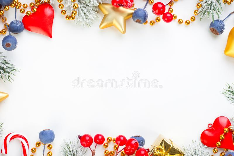 Christmas card border. Xmas composition frame with snowy green fir branch, red decorations and blue winter berries on white stock photo
