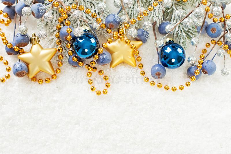 Christmas card border. Xmas composition with green fir branch, gold stars, blue baubles and berries on white snow background royalty free stock photography