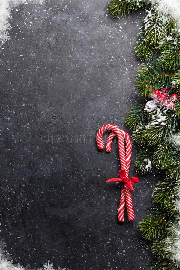 Christmas card with candy canes and fir tree. Branch covered by snow on stone background. Top view with space for your greetings royalty free stock photo