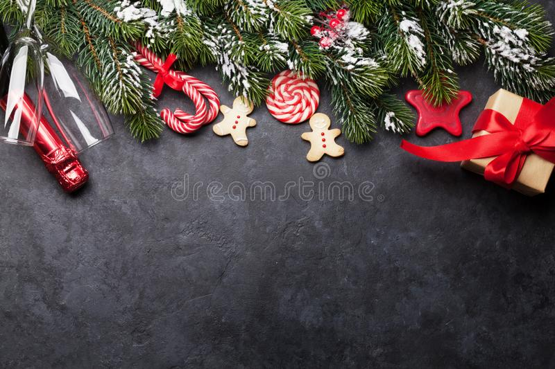 Christmas card with champagne and gift box. Christmas card with champagne, xmas gift box and fir tree branch covered by snow on stone background. Top view royalty free stock photos