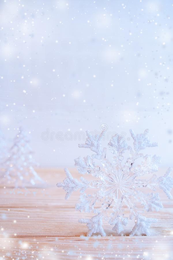 Christmas toy snowflake is standing on wooden table on pale blue background with snow. royalty free stock images
