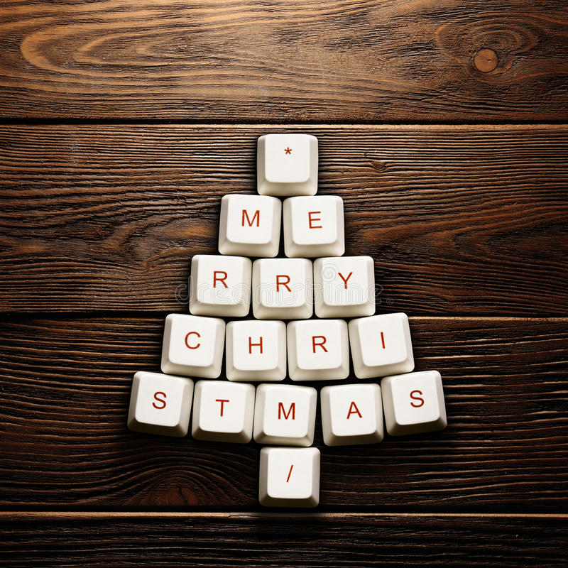 Christmas card - Christmas tree made of computer keys. Wooden background royalty free stock photography