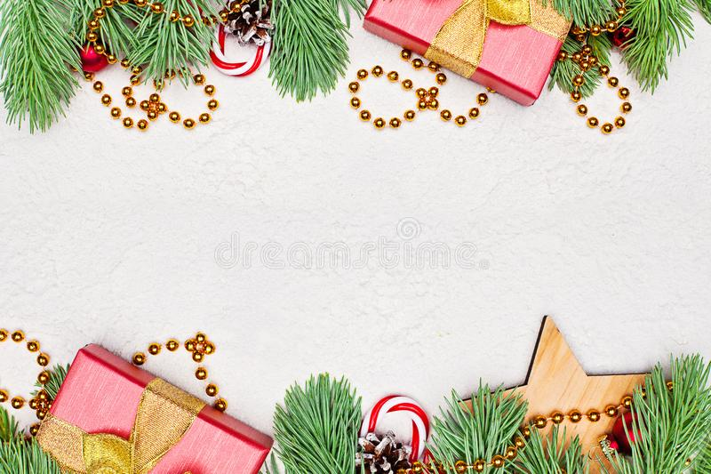 Christmas card composition border. Gold garland, green Xmas fir branch, red holly berries, gift and baubles. On white stucco plaster texture background royalty free stock photography