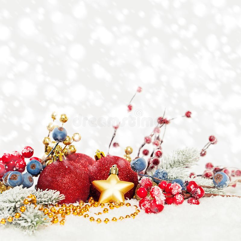 Christmas card composition. Evergreen Xmas tree twig, red holly berries, red baubles on white snow background.  stock photography