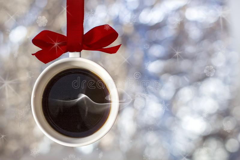 Christmas card- cup of fragrant hot coffee with smoke made from Christmas ball, bauble hangs on a red ribbon. On background of defocused silver lights. Concept royalty free stock photos