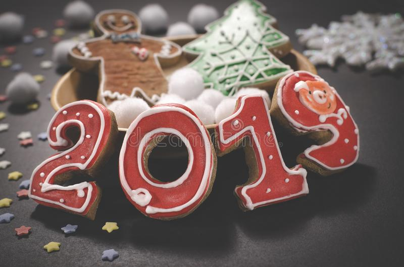 Christmas card on dark background gingerbread red numbers 2019 with slices of orange, multi-colored stars and gingerbread Man. Christmas card on dark background stock photo