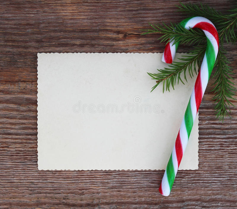Christmas card: empty paper form and candy cane with fir-tree br stock images