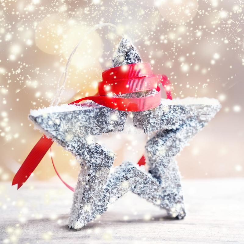 Christmas Card with festive star, snow and red ribbon on abstract defocused bokeh background. stock photos