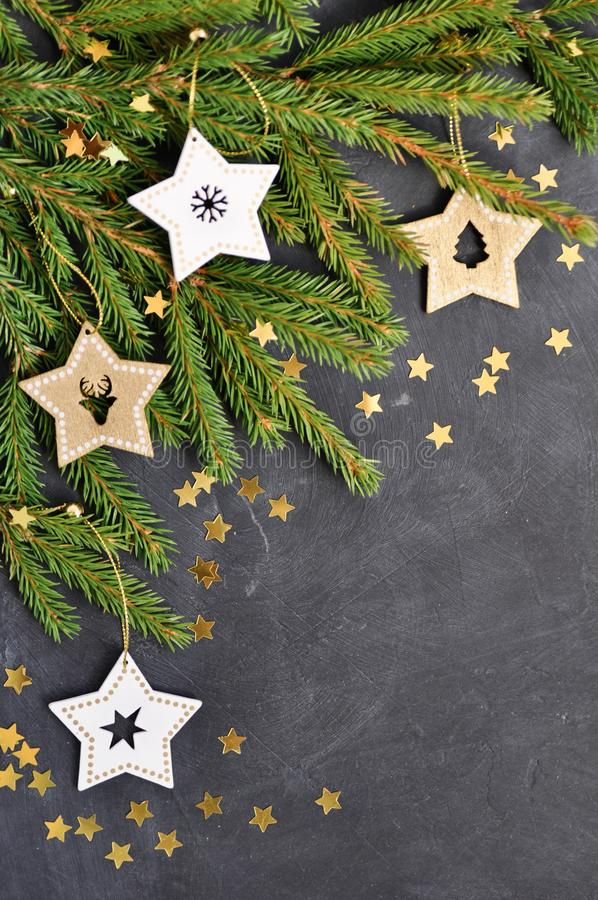 Christmas card with fir branches, wooden star decoration, gold confetti on dark background royalty free stock photo