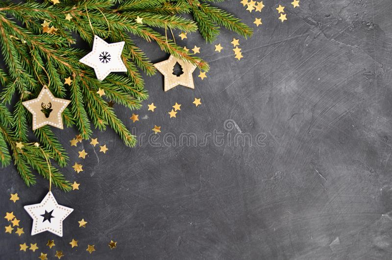 Christmas card with fir branches, wooden star decoration, gold confetti on dark background royalty free stock images