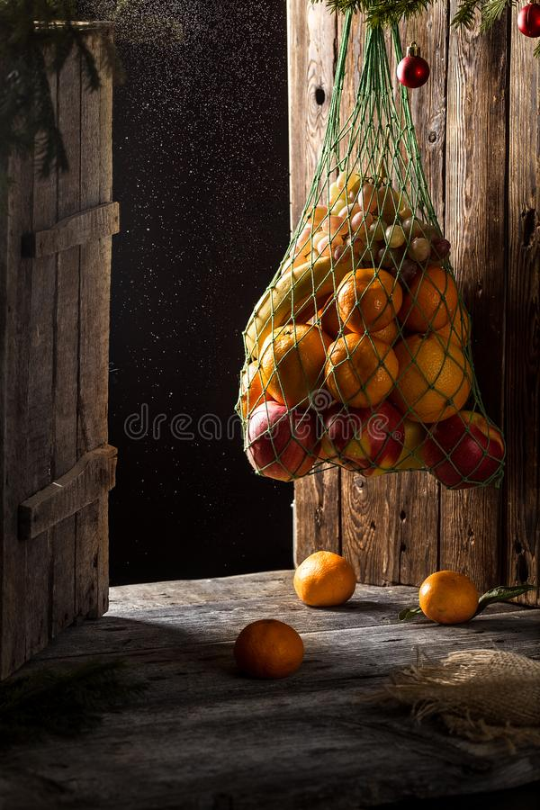 Christmas card with fruit. apples, oranges, tangerines, bananas. Christmas card with fruit on rustic wooden background. apples, oranges, tangerines, bananas royalty free stock photography