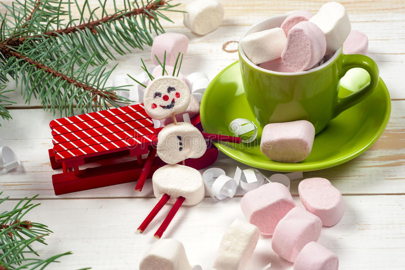 Christmas card with fun marshmallow snowman in green cup, tree stock image