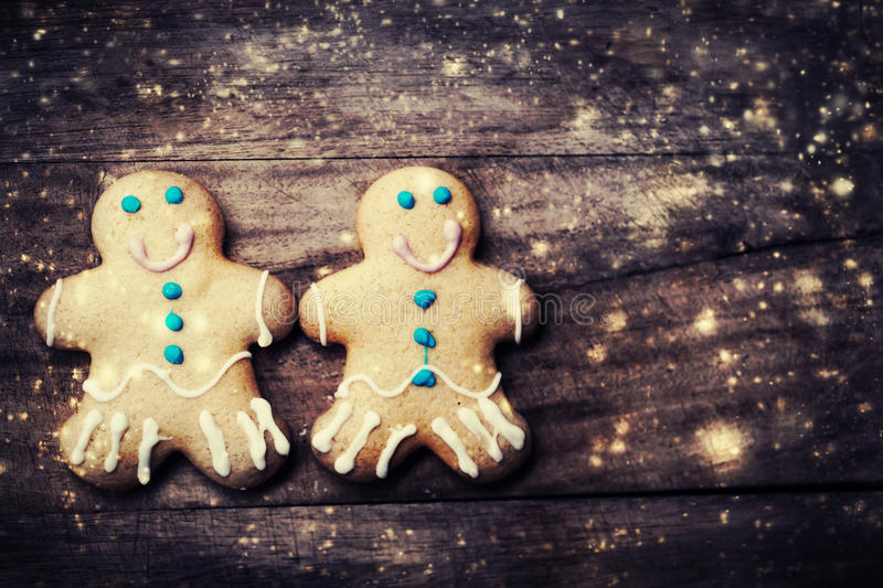 Christmas Card with gingerbread man cookies, decorations and falling snow with copy space over dark wooden background . stock photo