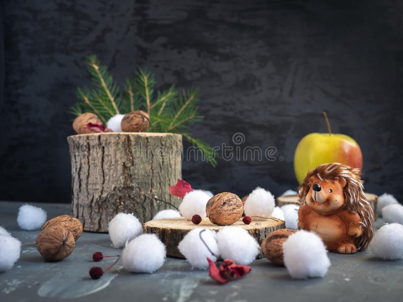 Christmas card. Hedgehog sits at hemp, on it is a large yellow-red apple, which he found on the forest hemp. Snowballs, dry autumn leaves stock photography