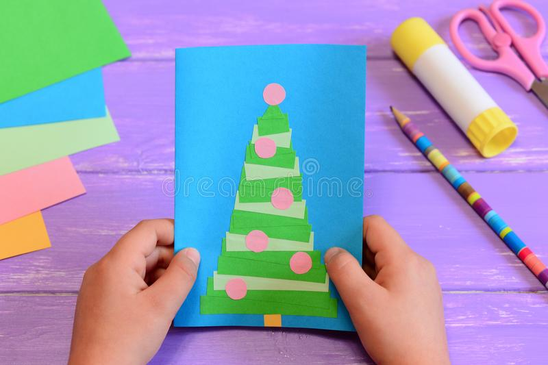 Child holds a Christmas greeting card in his hands. Child made a paper greeting card with a Christmas tree. Stationery on a table. Christmas card idea. Easy royalty free stock photo