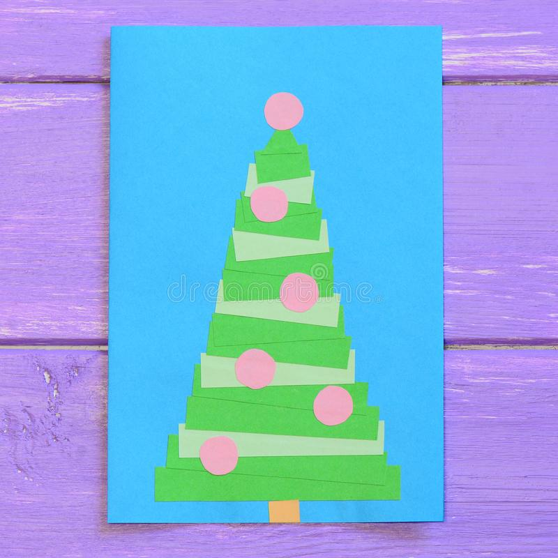 Christmas card isolated on purple wooden background. Greeting card with a Christmas tree. Easy paper crafts for children. Closeup stock photo