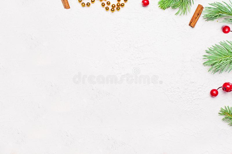 Christmas card modern minimal background. Corner composition with green Xmas fir branch, red holly berries and gold garland stock images