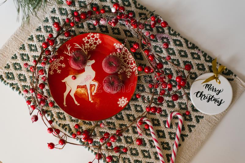Christmas card, new year flat lay. Red ceramic plate with sugar red apples, Christmas tree toy, candy cane and branches stock image
