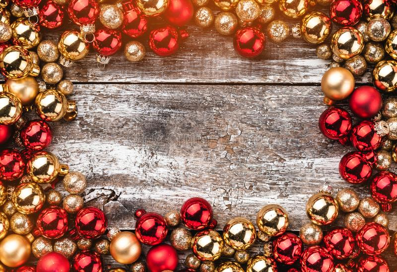 Christmas card. Old wooden background. Frame of red and gold baubles. Top view. Light effect.  royalty free stock photography
