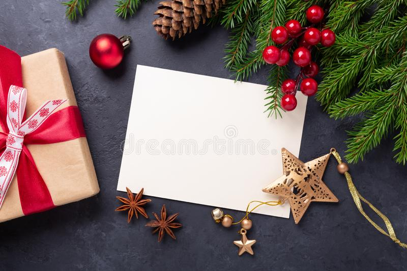 Christmas card with paper, gift box and fir tree branch on stone background. Holiday mockup. Top view. Image stock image