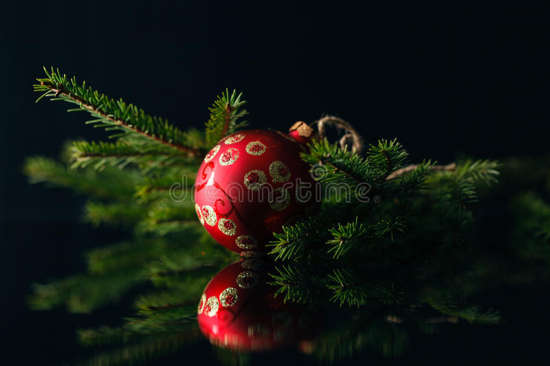 Christmas card with red baubles and fur tree on black background stock photos