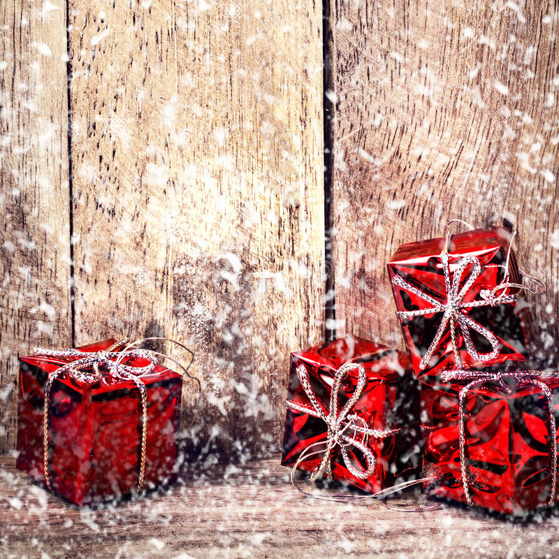 Christmas Card with Red Gift Boxes and falling snow on rustic wood board with copy space for greeting text. Festive decoration o stock photography