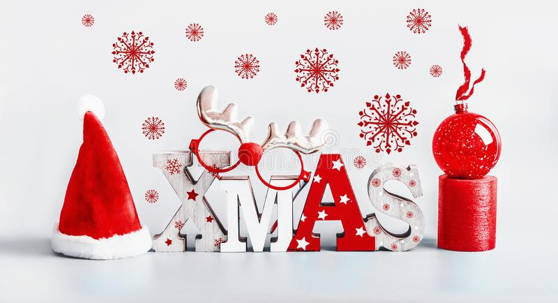 Christmas card with red snowflakes, Santa hut, word  Xmas, candles and red holiday ball stand on light gray background. Modern stock photography