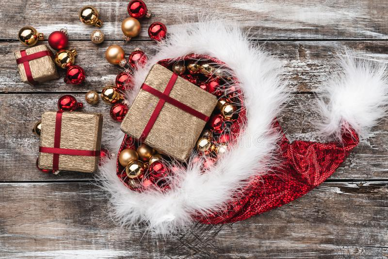 Christmas card. Santa`s hat full of baubles and gifts. Top view. Xmas Card royalty free stock photography