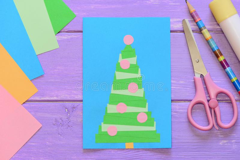 Christmas card, scissors, glue stick, pencil, colored paper on purple wooden background. Creative greeting card. Christmas card idea. Easy homemade christmas stock photography