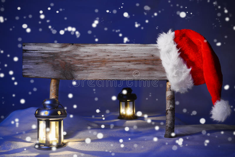 Christmas Card With Sign, Candlelight Santa Hat, Happy Holidays. Wooden Christmas Sign And Santa Hat With White Snow In Snowy Scenery. Copy Space Free Text For stock photo