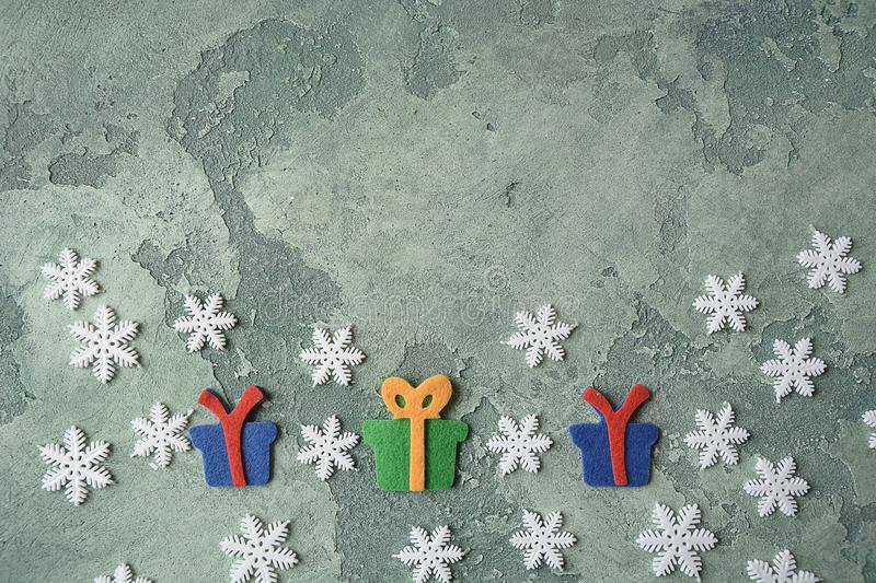 Christmas card. Snowflakes and felt giftboxes on green stone background. Top view. Copy space. Flat lay. Christmas concept. Holida stock photo