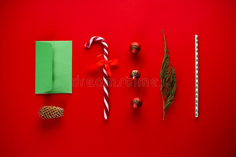 Christmas card of sweets and Christmas decorations on a red background with a green envelope. Flat lay stock photos