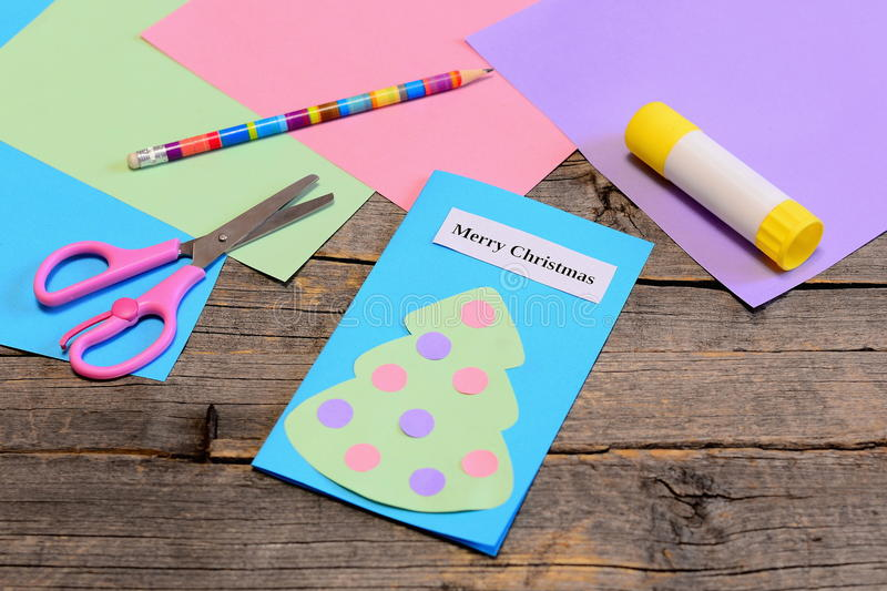 Christmas card tutorial. Paper greeting card with text Merry Christmas, pencil, glue stick, colored paper sheets, scissors royalty free stock photos