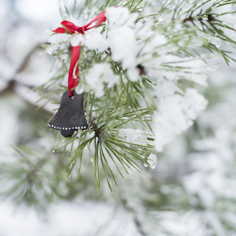 Christmas card  with Unique handmade black ceramic Christmas decoration shape of bell on pine tree. Festive wintertime background with Unique handmade Christmas stock photo