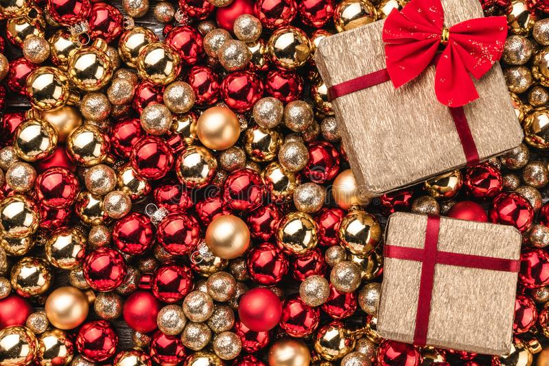Christmas card. Wallpaper of red and gold baubles. Top view. Gifts packed on one side.  royalty free stock photos