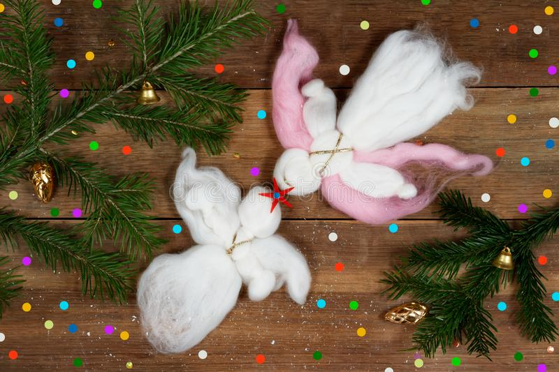 Christmas card: white woolen angels, colorful confetti and evergreen branches on wood plank. stock images