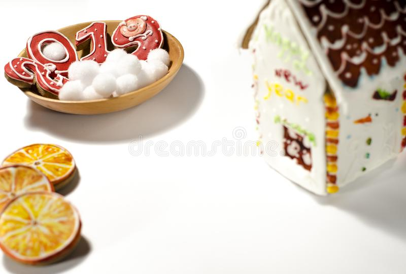 Christmas card: on a wooden plate are red ginger cookies in the shape of numbers 2019 and white round snowflakes stock photography