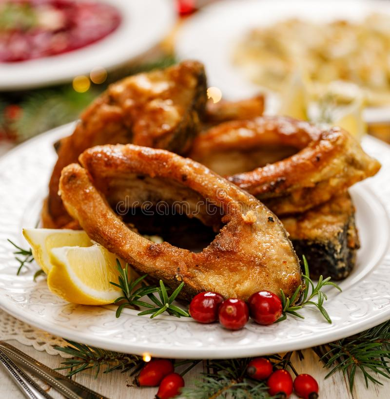 Christmas carp, Fried carp fish slices on a white plate, close up. royalty free stock images