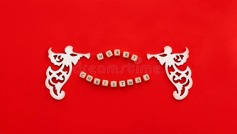 Christmas carved wooden angels with trumpet and words Merry Christmas on little bricks on red background. Christmas carved wooden angels with trumpet and words royalty free stock photography