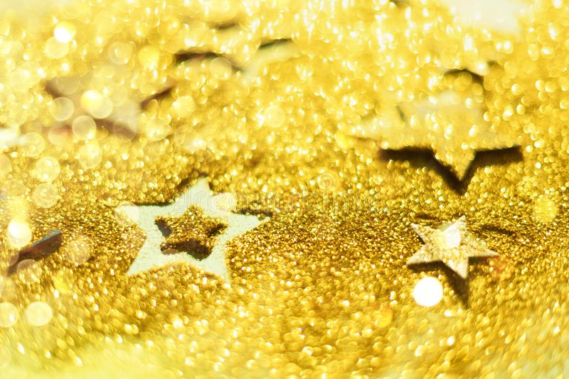 Christmas celebration. Abstract background for new year party. Patter of gold stars with lights, bokeh. Golden glitter stars on. Yellow shimmer texture royalty free stock photography