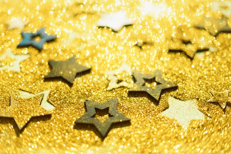 Christmas celebration. Abstract background for new year party. Patter of gold stars with lights, bokeh. Golden glitter stars on. Yellow shimmer texture stock images