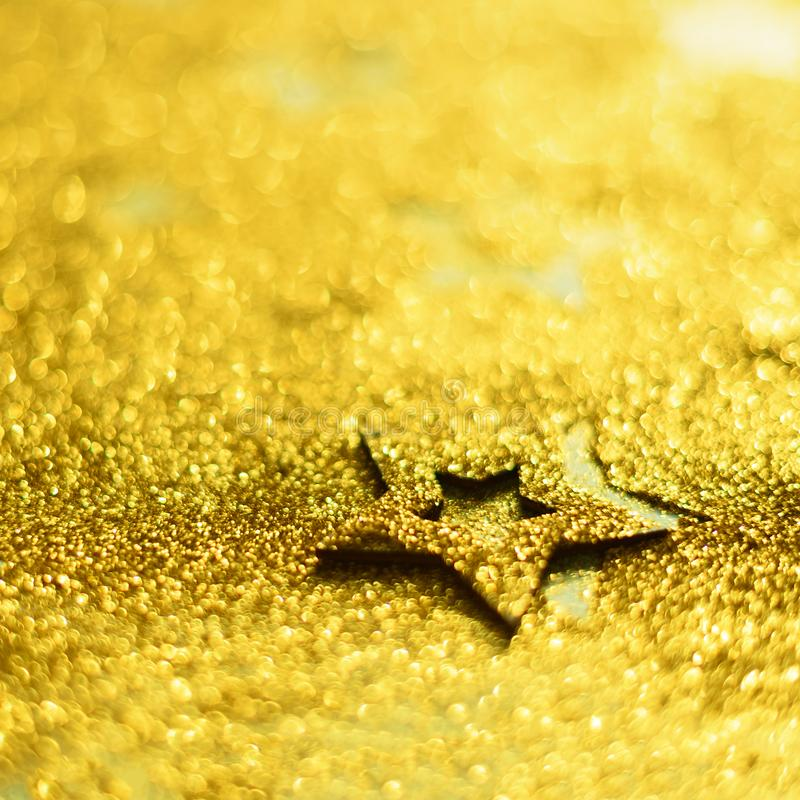 Christmas celebration. Abstract background for new year party. Patter of gold stars with lights, bokeh. Square crop. Golden. Glitter stars on yellow shimmer stock images