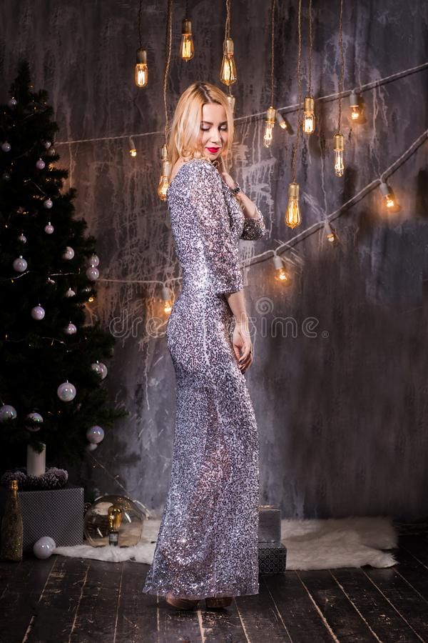 Christmas celebration. Beautiful young woman in the evening dress stands in a room decorated for Christmas and smiles. Christmas celebration. Beautiful young stock photo
