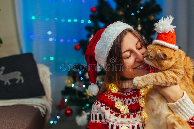 Christmas celebration with cat. Woman playing and kissing pet in Santa`s hat by New year tree at home stock photos